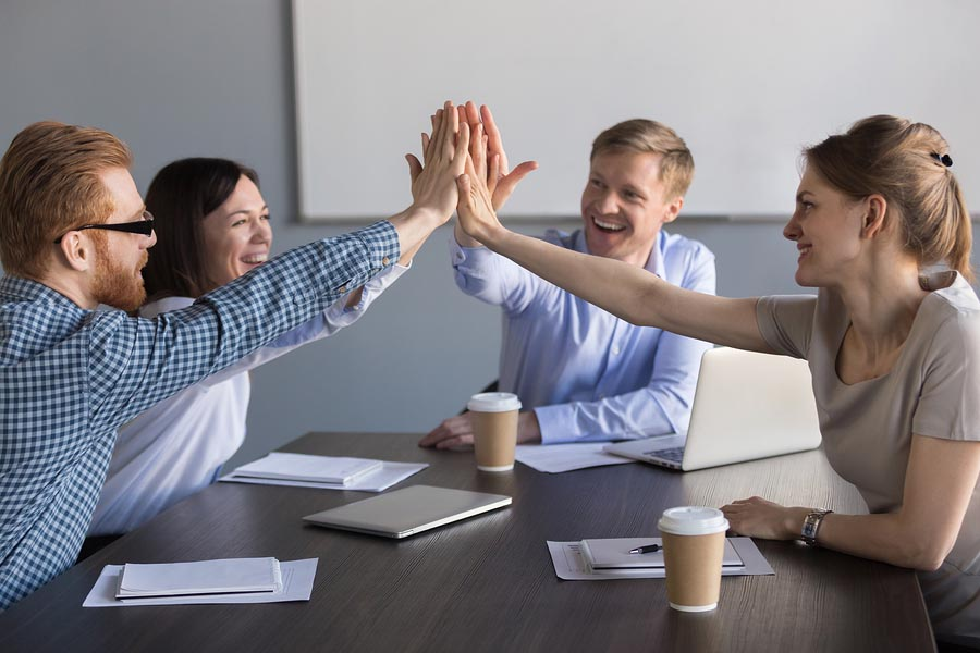 Excited Business Team Of Employees Giving High Five During Meeti